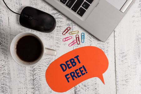 Conceptual hand writing showing Debt Free. Concept meaning does not owning any money to any individual or companies Metallic laptop speech bubble coffee cup on vintage table