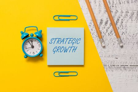 Text sign showing Strategic Growth. Business photo text create plan or schedule to increase stocks or improvement Notepad clips colored paper sheet markers alarm clock wooden background 免版税图像