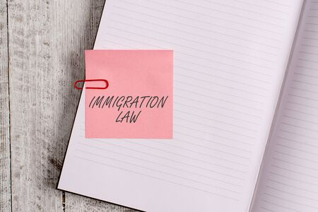 Writing note showing Immigration Law. Business concept for Emigration of a citizen shall be lawful in making of travel Notebook stationary placed above classic wooden backdrop
