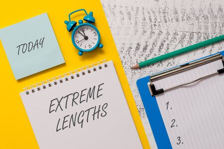 Conceptual hand writing showing Extreme Lengths. Concept meaning Make a great or extreme effort to do something better Spiral notepad sheet marker alarm clock wooden background