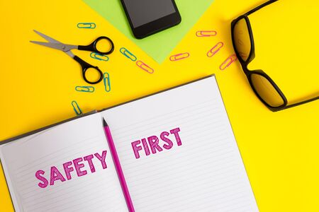 Word writing text Safety First. Business photo showcasing used to say that the most important thing is to be safe Sheet pencil clips smartphone scissors eyeglasses notepad color background