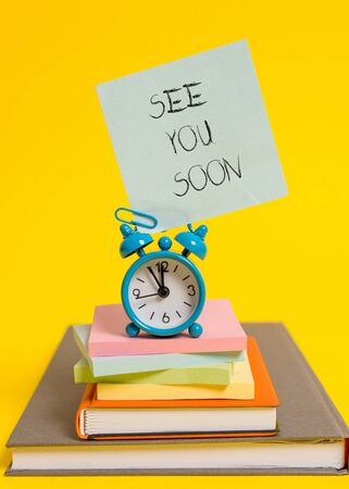 Handwriting text writing See You Soon. Conceptual photo used for saying goodbye to someone and going to meet again soon Alarm clock note stacked notepads old books colored background