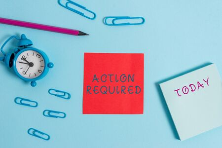 Writing note showing Action Required. Business concept for Regard an action from someone by virtue of their position Alarm clock wake up clips notepad sticky note pencil colored background Stock fotó