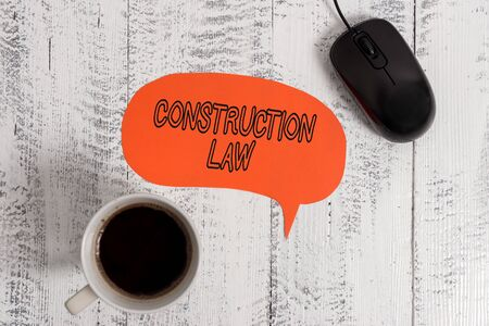 Conceptual hand writing showing Construction Law. Concept meaning deals with matters relating to building and related fields Wooden vintage table background coffee cup speech bubble