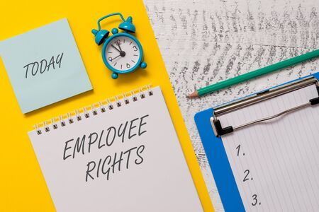 Conceptual hand writing showing Employee Rights. Concept meaning All employees have basic rights in their own workplace Spiral notepad sheet marker alarm clock wooden background