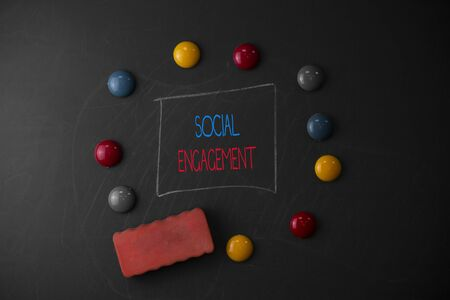 Conceptual hand writing showing Social Engagement. Concept meaning Degree of engagement in an online community or society Round Flat shape stones with same sizes stick black board