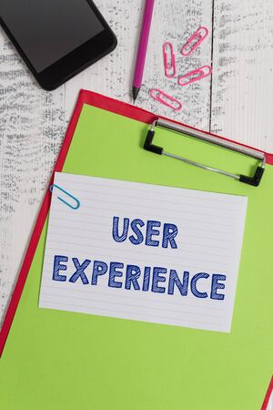 Writing note showing User Experience. Business concept for using website especially in terms how pleasing it is to use Clipboard sheet pencil smartphone squared note clips wooden background
