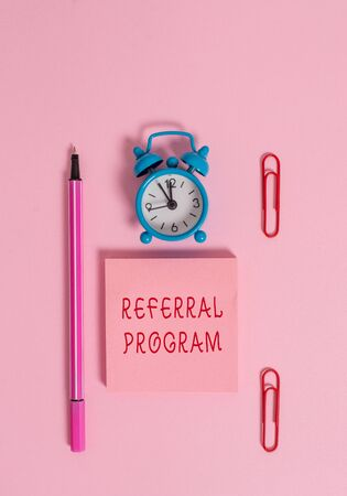 Conceptual hand writing showing Referral Program. Concept meaning employees are rewarded for introducing suitable recruits Metal alarm clock blank notepad marker clips colored background