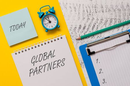 Conceptual hand writing showing Global Partners. Concept meaning Two or more firms from different countries work as a team Spiral notepad sheet marker alarm clock wooden background