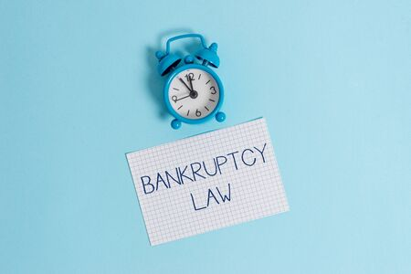Word writing text Bankruptcy Law. Business photo showcasing Designed to help creditor in getting the asset of the debtor Vintage alarm clock wakeup squared blank paper sheet colored background