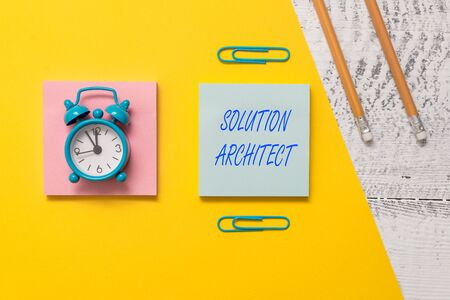 Conceptual hand writing showing Solution Architect. Concept meaning Design applications or services within an organization Notepads colored paper sheet markers alarm clock wooden background Фото со стока