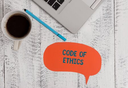 Text sign showing Code Of Ethics. Business photo showcasing basic guide for professional conduct and imposes duties Metallic open laptop speech bubble coffee cup ballpoint pen vintage table