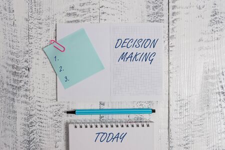 Word writing text Decision Making. Business photo showcasing The act of deciding between two or more possibilities Open squared spiral notepad clip note highlighter lying old wooden background