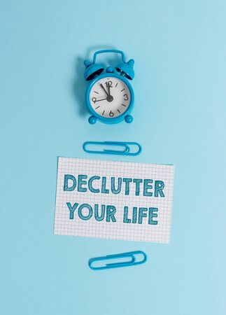 Handwriting text writing Declutter Your Life. Conceptual photo To eliminate extraneous things or information in life Alarm clock wakeup squared blank paper sheet clips colored background 写真素材