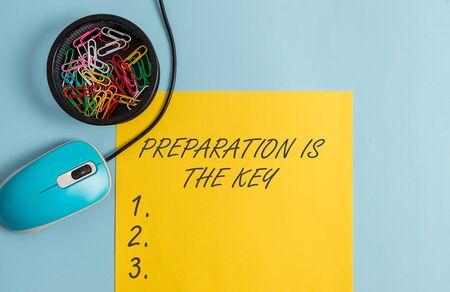 Conceptueel handschrift met voorbereiding is de sleutel. Concept, wat betekent dat het fouten vermindert en de activiteiten verkort Notitieboekje en briefpapier met gadgets boven een pastelkleurige achtergrond