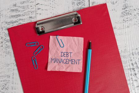 Writing note showing Debt Management. Business concept for The formal agreement between a debtor and a creditor Colored clipboard crushed sticky note clip marker old wooden background 写真素材