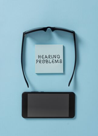 Handwriting text writing Hearing Problems. Conceptual photo is partial or total inability tolisten to sounds normally Dark eyeglasses colored sticky note smartphone fashion pastel background