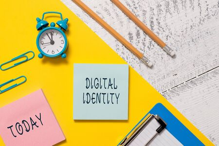 Word writing text Digital Identity. Business photo showcasing information on entity used by computer to represent agent Notepads clips paper sheet clipboard markers alarm clock wooden background