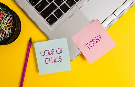 Text sign showing Code Of Ethics. Business photo text basic guide for professional conduct and imposes duties Trendy metallic laptop sticky notes clips container pencil colored background 스톡 콘텐츠