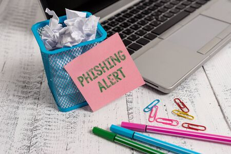 Writing note showing Phishing Alert. Business concept for aware to fraudulent attempt to obtain sensitive information Laptop sticky note waste basket crushed paper clips pens vintage table