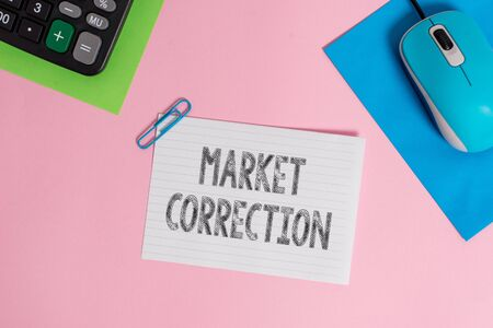Conceptual hand writing showing Market Correction. Concept meaning When prices fall 10 percent from the 52 week high Wire electronic mouse calculator paper colored background Archivio Fotografico