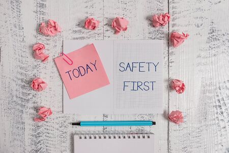 Text sign showing Safety First. Business photo text used to say that the most important thing is to be safe Squared spiral notepad clip note highlighter paper balls wooden background 스톡 콘텐츠