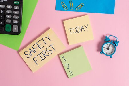 Conceptual hand writing showing Safety First. Concept meaning used to say that the most important thing is to be safe Alarm clock calculator notepads paper sheet color background