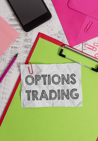 Conceptual hand writing showing Options Trading. Concept meaning Different options to make goods or services spread worldwide Clipboard sheet pencil smartphone clips notepad wooden back