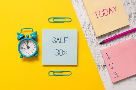 Handwriting text writing Sale 30 Percent. Conceptual photo A promo price of an item at 30 percent markdown Notepads clips colored paper sheet marker alarm clock wooden background