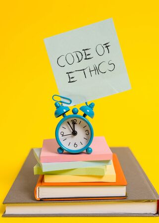 Handwriting text writing Code Of Ethics. Conceptual photo basic guide for professional conduct and imposes duties Alarm clock note stacked notepads old books colored background 스톡 콘텐츠