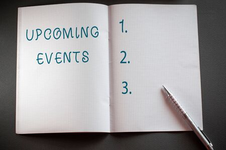 Word writing text Upcoming Events. Business photo showcasing the approaching planned public or social occasions Checkered math book and classic silver pen placed above textured work desk Stock Photo