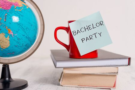Writing note showing Bachelor Party. Business concept for Party given for a analysis who is about to get married Stag night Globe map world earth cup blank sticky note stacked books wooden table Foto de archivo
