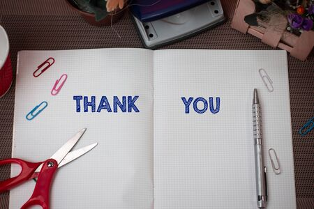 Writing note showing Thank You. Business concept for a polite expression used when acknowledging a gift or service Scissors and writing equipments plus math book above textured backdrop