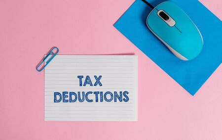 Text sign showing Tax Deductions. Business photo showcasing an amount or cost that subtracted from someone s is income Wire electronic mouse striped blank paper sheets clip colored background