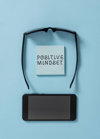 Handwriting text writing Positive Mindset. Conceptual photo mental and emotional attitude that focuses on bright side Dark eyeglasses colored sticky note smartphone fashion pastel background