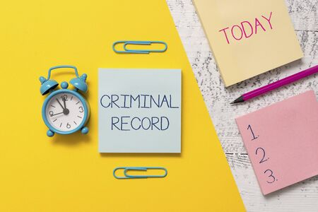 Handwriting text writing Criminal Record. Conceptual photo profile of a demonstrating criminal history with details Notepads clips colored paper sheet marker alarm clock wooden background Stockfoto