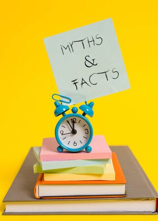 Handwriting text writing Myths And Facts. Conceptual photo usually traditional story of ostensibly historical events Alarm clock note stacked notepads old books colored background