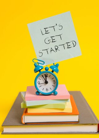 Handwriting text writing Let S Is Get Started. Conceptual photo to begin doing or working on something you had started Alarm clock note stacked notepads old books colored background