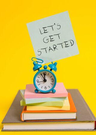Texte de l'écriture écrit Let S est de commencer. Photo conceptuelle pour commencer à faire ou à travailler sur quelque chose que vous aviez commencé Réveil note bloc-notes empilés vieux livres fond coloré Banque d'images