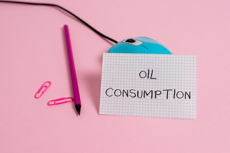 Word writing text Oil Consumption. Business photo showcasing This entry is the total oil consumed in barrels per day Wire vintage mouse clips marker squared paper sheet colored background Фото со стока