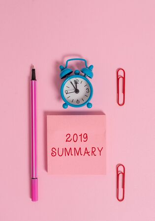 Conceptual hand writing showing 2019 Summary. Concept meaning brief comprehensive especially covering the main points of 2019 Metal alarm clock blank notepad marker clips colored background
