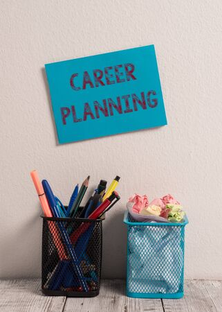 Word writing text Career Planning. Business photo showcasing Strategically plan your career goals and work success Blue Sticky Card on Wall Two Pencil Pots Pens Pencils Markers Waste Paper