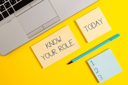 Conceptual hand writing showing Know Your Role. Concept meaning end acting outside who you actually are Play your position Silver laptop square sticky notepads marker colored background Stock Photo