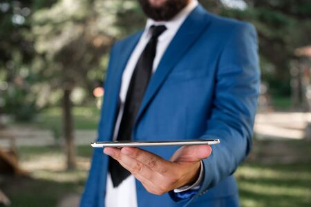 Businessman in blue suite stands with mobile phone in hands.