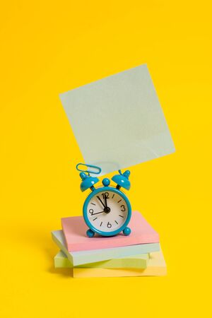 Metal alarm clock blank sticky note stacked notepads colored background