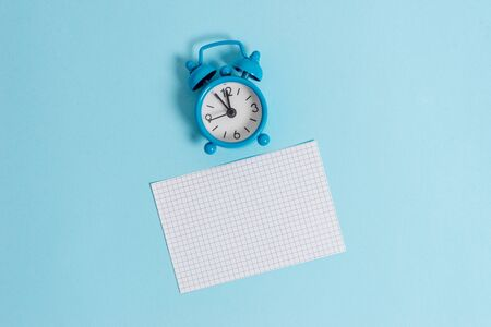 Vintage alarm clock wakeup squared blank paper sheet colored background