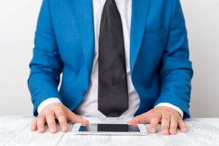 Businessman in blue suite with a tie holds lap top in hands. Imagens
