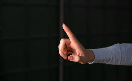 Finger pointing in the empty space. Dark background with hand pointing in the copy space.