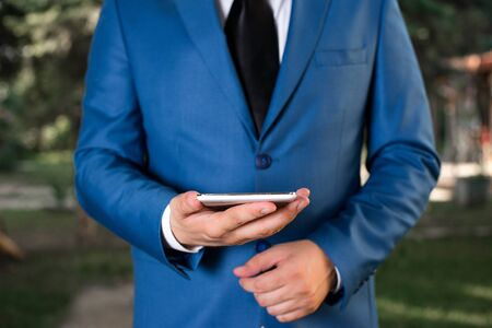 Businessman in blue suite stands with mobile phone in hands. Imagens
