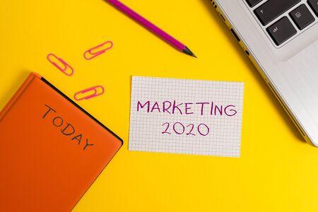 Escritura de texto escrito Marketing 2020.Foto conceptual Tendencias comerciales para el evento promocional de Año Nuevo 2020 Clips para portátiles Lápiz Hoja de papel Cuaderno de tapa dura Fondo de color